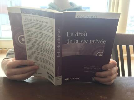 Un étudiant lit un livre sur le droit de la vie privée pour connaître ses droits.
