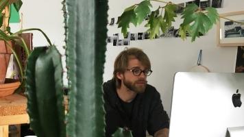 Le photodocumentariste Renaud Philippe retouche ses photos dans son petit bureau enveloppé de plantes.