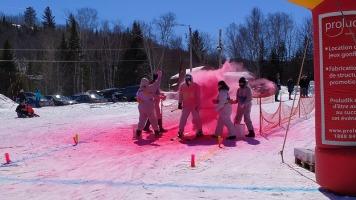 Skieurs et planchistes ont dévalé les pentes pour l'événement Descente en couleurs à la station de ski Val Saint-Côme. Un participant est aspergé de poudre colorée par l'équipe de bénévoles. Photos: Naomy Thériault.